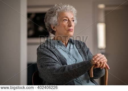 Retired unhappy woman at home. Lonely serious senior woman holding wooden walking stick and looking through the window. Moody and upset grandmother sitting on couch in nursing home.