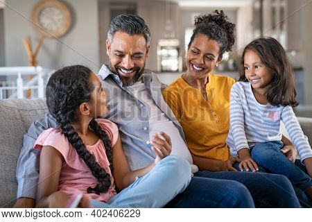 Cheerful multiethnic family at home sitting on sofa listening to daughter. Happy couple with two girls relaxing at home together. Smiling indian parents talking to their daughter in the living room.