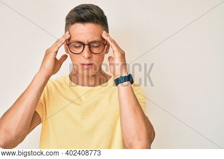Young hispanic boy wearing casual clothes and glasses suffering from headache desperate and stressed because pain and migraine. hands on head.