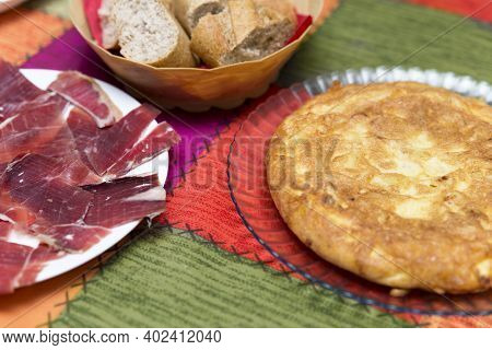 Close-up Of Plates With Spanish Potatoes Omelete And Serrano Ham Served