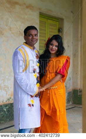 Happy Asian Indian Couple Wearing Colorful Traditional Ethnic Outfits Looking Forward And Smiling. B