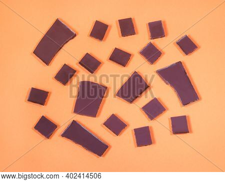 Food Pattern Made Of Dark Chocolate Chunks On Orange Background. Top View.