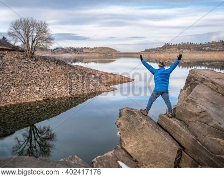 happy male hiker on a rocky shore of a mountain lake at foothills of Rocky Mountains, Horsetooth Reservoir - a popular recreational area in northern Colorado in falll or winter scenery