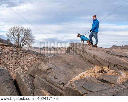 senior male hiker is waling with pitbull dog on a shore of mountain lake at foothills of Rocky Mountains, Horsetooth Reservoir - a popular recreational area in northern Colorado in fall or winter