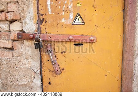 Locked Old Rusty Yellow Door With High Voltage Sign. Grey Wall Of Transformer Substation And Closed