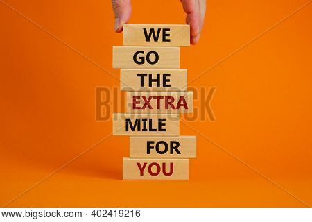 Go The Extra Mile Symbol. Wooden Blocks With Words 'we Go The Extra Mile For You'. Male Hand. Beauti