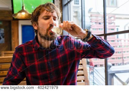 Lonely Man Drinking Strong Alcohol In A Bar. A Person In Depression, In Despair, Drinks An Alcoholic