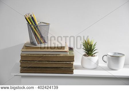 Pencil Holder With Crayons On Stack Of Old Vintage Books Lying On Mantelpiece. Artificial Aloe In Ce