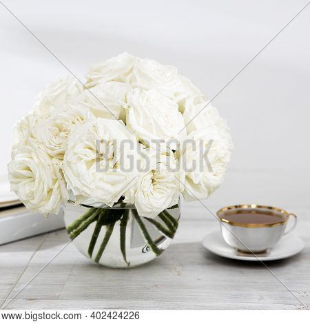 A Bouquet Of White Roses In A Round Glass Vase On A Table With Cup Of Tea And Book. Copy Space