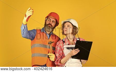 Family Counting Finances For Renovation. Couple Looking At Documents. Woman And Man Wear Safety Hard