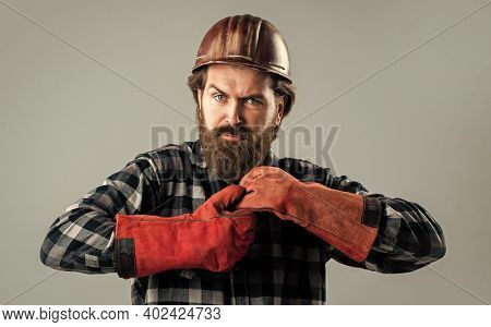 Serious And Confident Serviceman. Brutal Hipster Man. Man In Hard Hat. Engineer In Gloves. Construct