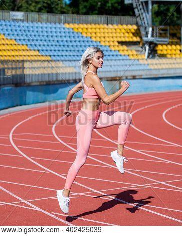 Sport Woman In Sportswear Sprinting On Stadium Running Track Before Training Fitness, Stamina