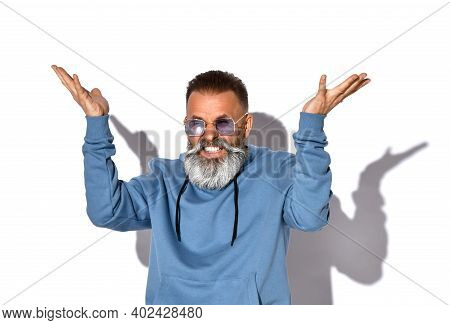 Irritated Emotional Gray-haired Bearded Man In Fashionable Sunglasses, Casual Sweatshirt Looks Into