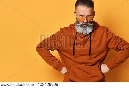 Frowning Menacing Fed-up Brutal Grey-haired Bearded Man In Sportswear And Trendy Sunglasses Standing