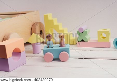 Little People Made Of Wood. The Car Is Blue With Pink Wheels. Children's Toys Made Of Natural Materi