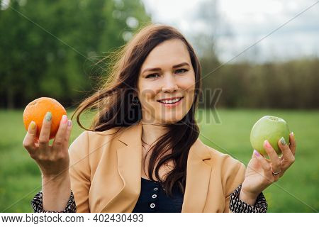 Woman Deciding Between Two Fruits An Apple And An Orange. Healthy Eating. A Healthy Lifestyle