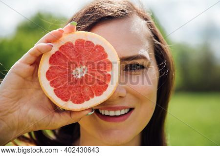 Portrait Of Woman Covering Her Eye With Grapefruit.