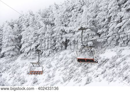 Empty Chairlift In Mountain Landscape Covered With Snow. Space For Text.