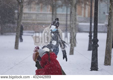 Madrid, Spain - January 08, 2021: Happy People Playing To Throw Snowballs In The Buen Retiro Park In