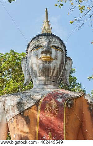 Phayao, Thailand - Dec 6, 2020: Portrait Zoom View Front Buddha Statue In Green Forest And Blue Sky