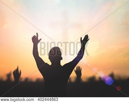 Praise And Worship Concept: Silhouette Human Raising Hands To Praying God On Blurred Cross With Crow
