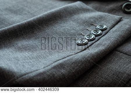 ฺblurred Defocus Shot Of Formal Black Or Dark Grey Wool Suit Fabric Texture. With Button Decoration