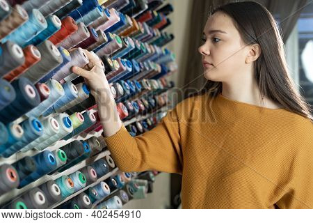 A Beautiful Woman Seamstress Holds Her Hand On A Bobbin With Threads. The Color Of The Suit Is Chose