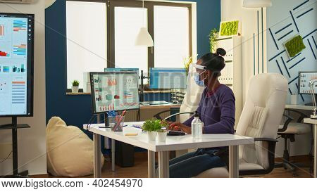Black Employee With Protection Mask And Visor Cleaning Hands With Sanitizer Gel Before Writing At Co