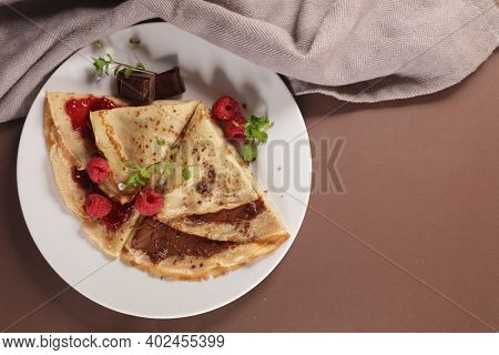 crepe with chocolate spread and raspberry fruit jam