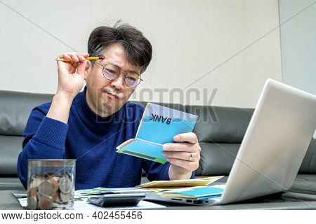 Middle-aged Asian man preparing for tax return.