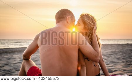 Couple On Beach Kissing In Sunset. People In Vacation. Beautiful Couple On Beach In Vacation In Suns