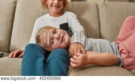 Portrait Of Cute Little Girl Smiling At Camera While Spending Time Together With Her Sibling Brother