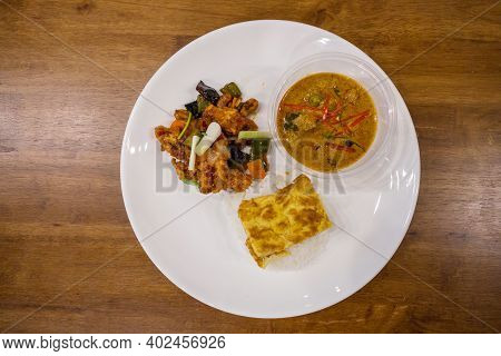 Rice With Panaeng Curry With Pork,  Stir Fried Chicken With Cashew Nuts And Omelette On Wooden Table