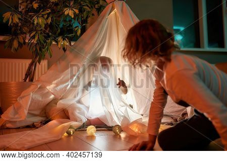 Two Cheerful Kids, Brother And Sister Playing Together At Home. Little Girl Playing Ghost While Sitt