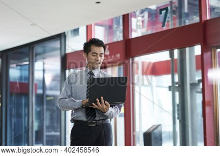 Asian Businessman Standing In Company Lobby Checking Email Using Laptop Computer