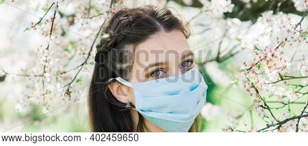 A Girl In Protective Medical Mask In Spring Among The Blooming Garden. . Spring Allergy Conception