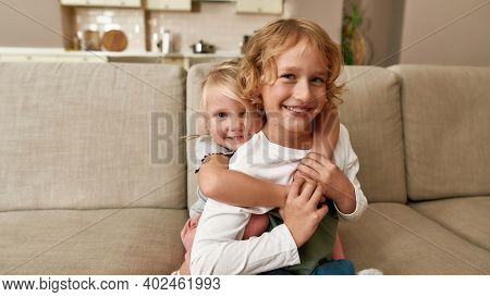 Portrait Of Joyful Siblings, Little Boy And Girl Smiling At Camera, Embracing Each Other While Sitti