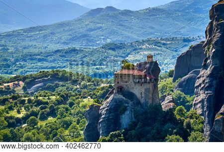 Close View Of Monastery Of St Nicholaos Anapafsas On Top Of Sedimentary Pillar, Green Hills Of Meteo