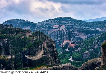View On Pillars Of Sedimentary Rocks In Famous Meteora Valley At Overcast Day. Roussanou Nunnery And