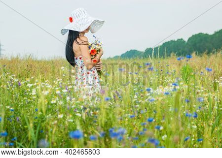 Young Lady Going Across Meadow. A Girl With Long Dark Hair In A Colored Dress And A White Hat With P