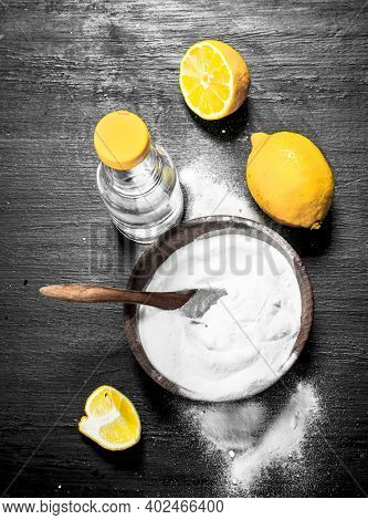 Baking Soda In A Bowl With Vinegar And Lemon Slices. On The Black Chalkboard.