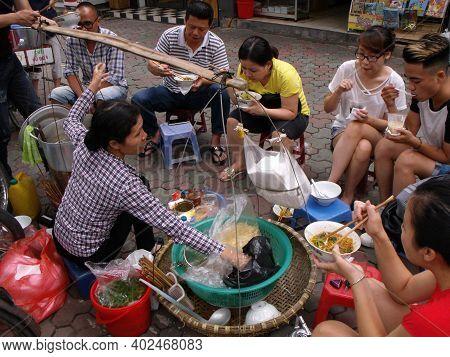 Hanoi, Vietnam, June 16, 2016: Several People Eat Noodles At A Hanoi Street Food Stall