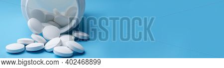 Medicine Stethoscope And Pills On Blue Background. Health Or Disease.