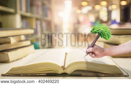 Teacher Day Concept: Student Hand Holding Pencil Of Tree And Writing On Old Book In Blurred Library