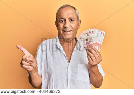 Handsome mature man holding 10 colombian pesos banknotes smiling happy pointing with hand and finger to the side