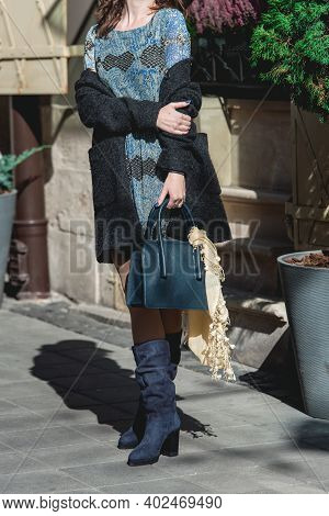 Stylish Fashionable Woman In Dark Blue Suede Boots And Dress. Girl In Winter Boots With Leather Bag