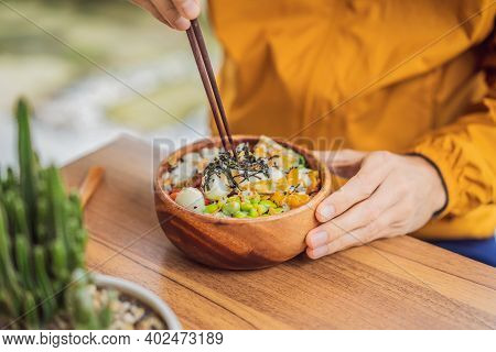 Man Eating Raw Organic Poke Bowl With Rice And Veggies Close-up On The Table. Top View From Above Ho