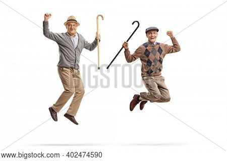 Full length portrait of two happy elderly men holding walking canes and jumping isolated on white background
