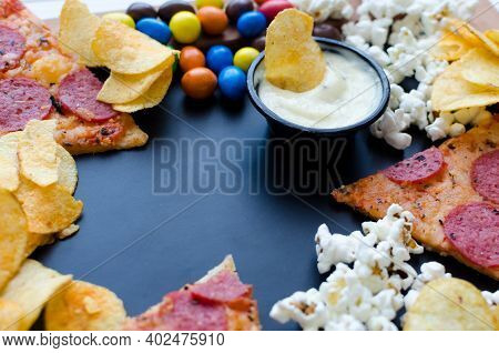 Fast Food And Unhealthy Eating Concept. Close Up Of Fastfood Snacks: Pizza, Popcorn, Potato Chips An