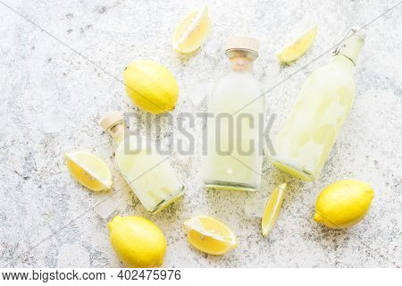 Bottles With Traditional Frozen Homemade Lemon Liqueur Limoncello And Fresh Citrus On The Table. Ita